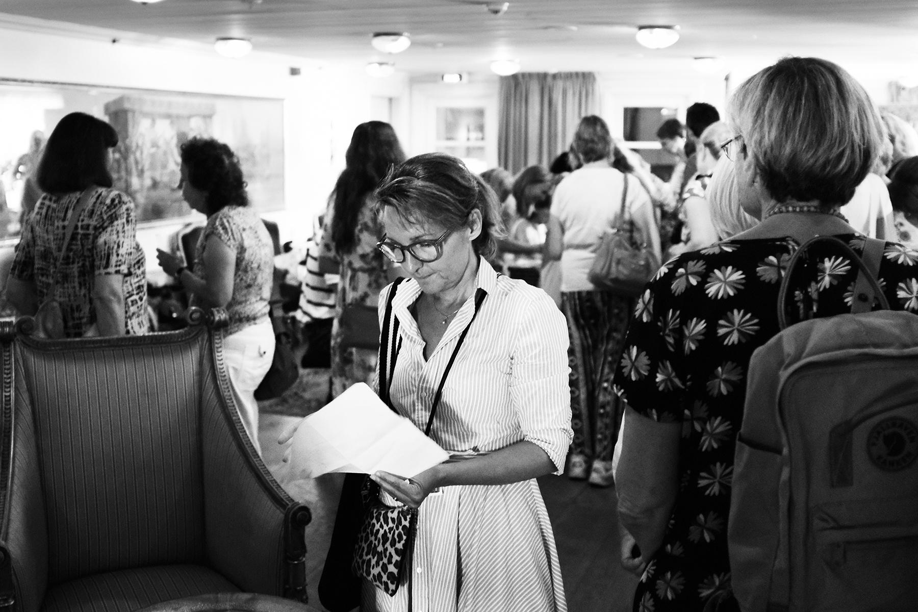 Lina Lodegård Sjögren på Norstedts förlag läser i papper i rum fullt av besökare.