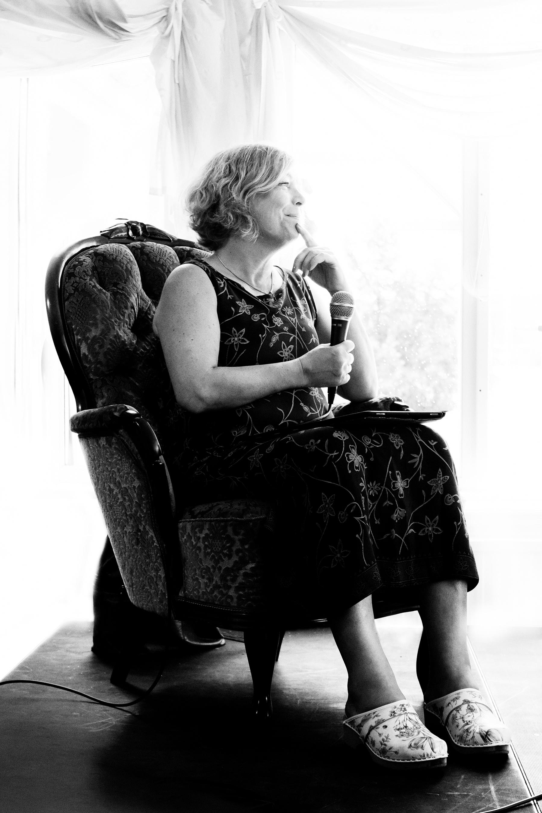 Ann Ljungberg modererar samtal på scenen från en antik fåtölj.