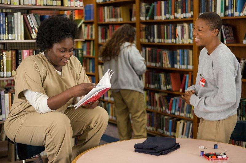 Taystee och Poussey är glada i fängelsebiblioteket.