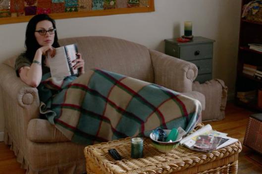 Alex sitter i soffa i en lägenhet, håller en bok.