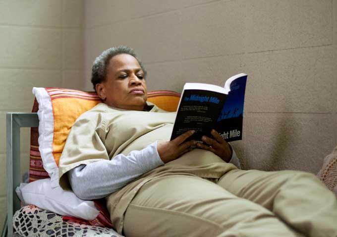 """Miss Claudette i ointb ligger på sin säng och läser """"The midnight Mile"""""""
